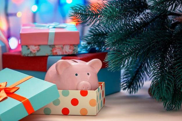 Piggy bank sous un arbre de noël dans une boîte de vacances
