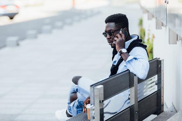 Un pigiste africain heureux parle par téléphone dans la rue, assis dans les escaliers.