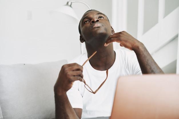 Pigiste afro-américain avec ordinateur portable à la maison