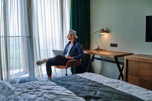 Un pigiste caucasien décontracté du millénaire s'assoit sur une chaise dans une chambre d'hôtel et travaille à distance en ligne avec un ordinateur portable