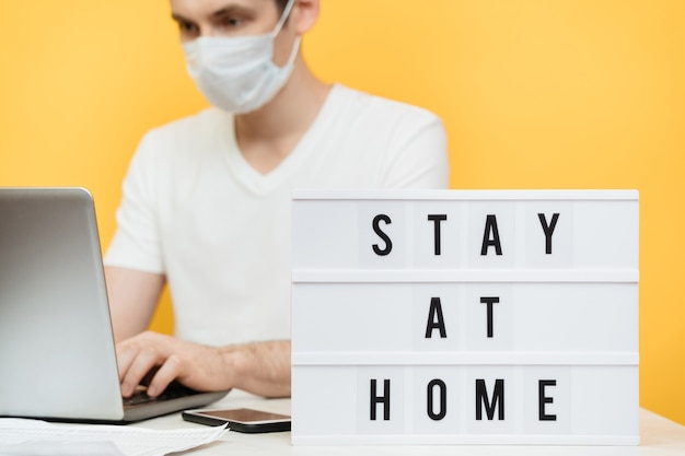 Un pigiste caucasien sérieux dans un masque protecteur fonctionne à distance avec un ordinateur portable et un smartphone pendant la quarantaine du coronavirus