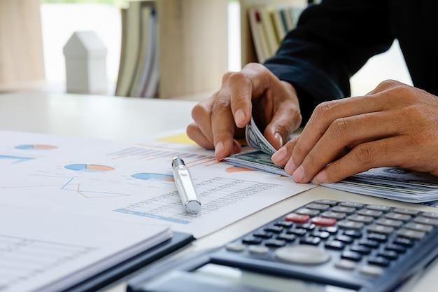 Pigiste comptant de l'argent ou des dollars dans le bureau tout en travaillant sur un ordinateur portable ou un ordinateur.