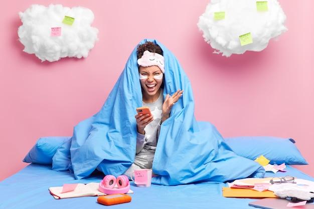 Le pigiste crie fort utilise un téléphone portable avec une couverture subit des procédures de beauté reste et travaille depuis le lit prend des notes sur des notes autocollantes isolées sur un mur rose