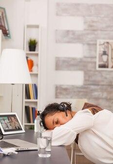 Une pigiste avec des écouteurs dormant sur le bureau lors d'un appel vidéo.