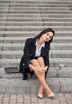 La pigiste est une entrepreneure avec un ordinateur portable dans les escaliers, elle fait une pause