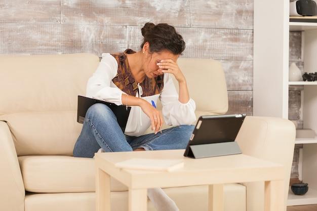 Une pigiste fatiguée travaillant à domicile lors d'une vidéoconférence.