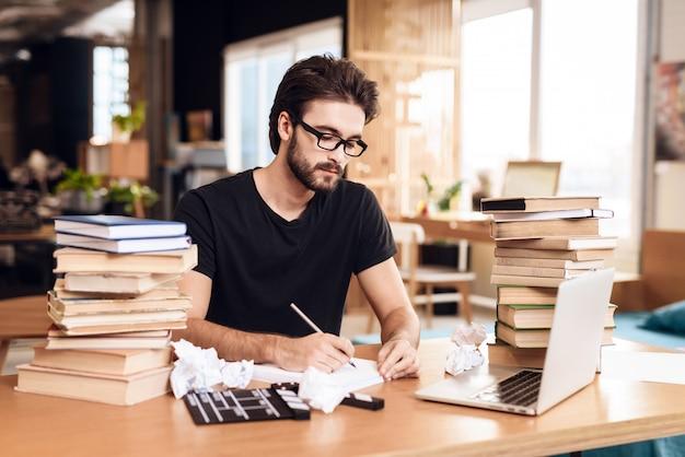 Pigiste homme barbu prenant des notes, assis au bureau.