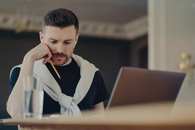 Pigiste masculin concentré dans des écouteurs sans fil et des vêtements décontractés se concentrant sur le travail, tenant un crayon et lisant un rapport tout en étant assis sur un lieu de travail confortable avec un ordinateur portable, travaillant à distance depuis la maison