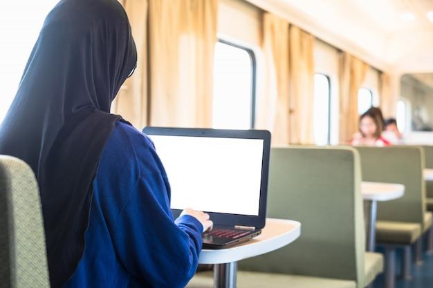 Pigiste musulmane travaillant avec un ordinateur portable dans un train.