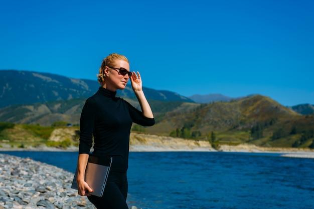 Pigiste avec ordinateur portable sur la nature. blogger hipster voyageur business lady jolie fille a terminé son travail en plein air. jeune femme blonde avec des lunettes de soleil en noir debout à côté de la rivière de montagne