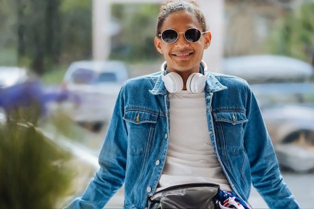 Un pigiste à la peau foncée heureux portant des lunettes élégantes tout en regardant la caméra
