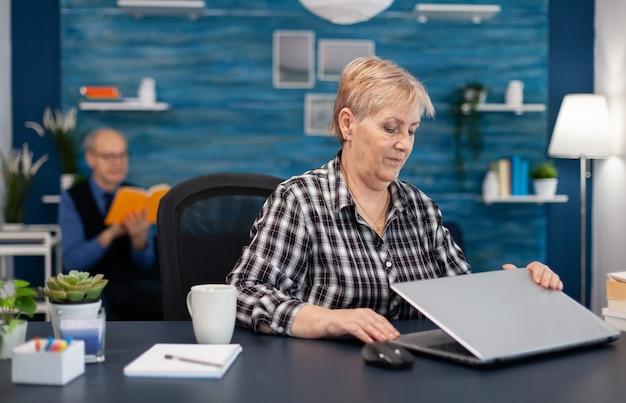 Un pigiste senior positif ouvrant un ordinateur portable assis au bureau à domicile et un mari mûr lisant un livre