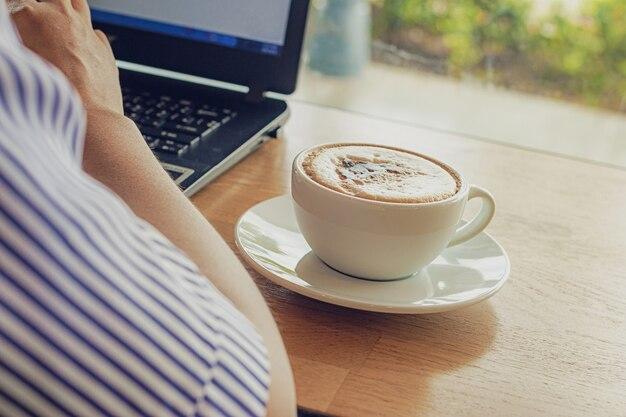 Pigiste travaillant au café sur un comptoir en bois avec des tasses à café et un ordinateur portable.