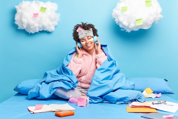 Un pigiste travaille à domicile est assis dans son lit porte un pyjama écoute de la musique via un casque prend des notes utilise des autocollants isolés sur bleu