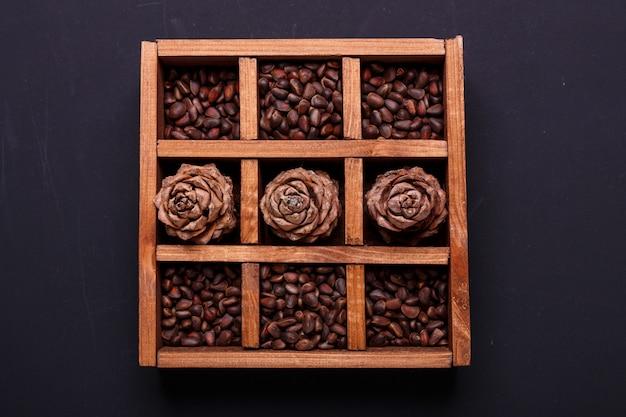 Des pignons et des cônes dans une boîte en bois sur une ardoise noire. vue de dessus.