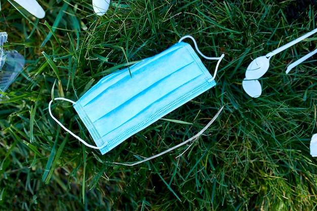 Piile d'ordures éparpillées sur fond d'herbe verte