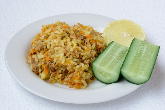 Pilaf appétissant, savoureux, chaud et frais (pilau, pilaw, pilaff) sur une assiette avec deux concombres et une tranche de citron. pilaf au boeuf, carottes, oignons, ail sur fond blanc. un plat traditionnel d'asie.