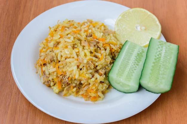 Pilaf appétissant, savoureux, chaud et frais (pilau, pilaw, pilaff) sur une assiette avec deux concombres et une tranche de citron. pilaf au boeuf, carottes, oignons, ail sur fond de bois. un plat traditionnel asiatique.
