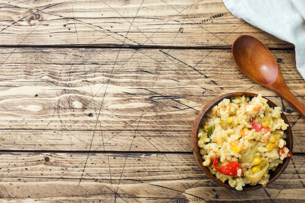 Pilaf aux légumes et au poulet dans un bol en bois sur fond de bois.