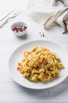 Pilaf avec des légumes et du poulet dans une assiette grise sur une lumière.