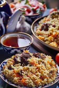 Pilaf ouzbek dans un authentique plat bleu et or, tourné sur fond bleu avec des tomates, de l'ail et du thé