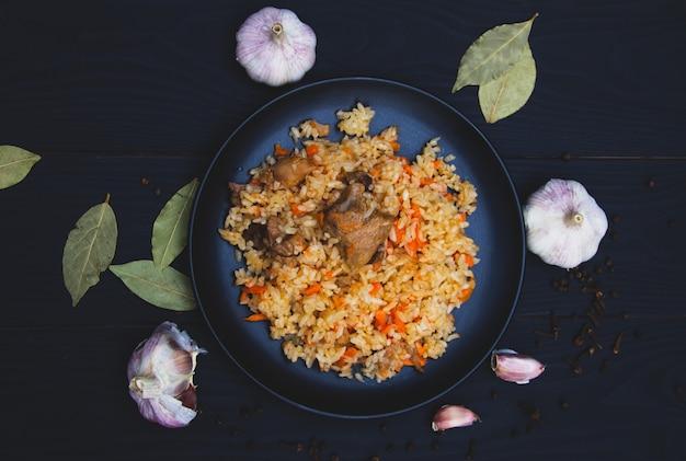 Pilaf traditionnel savoureux à l'ail et aux épices sur plaque noire. plat national du kazakhstan. vue de dessus.