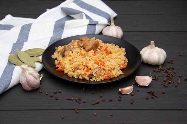 Pilaf traditionnel savoureux à l'ail et aux épices sur plaque noire. plat national ouzbek.