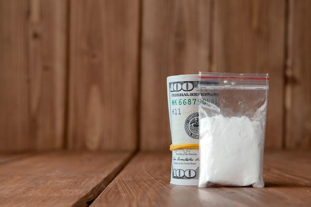 Pile d'argent, de drogue et sur une table en bois.