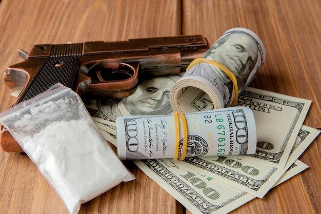 Pile d'argent, de drogues et d'une arme à feu sur une table en bois, concept sur le danger et la menace de la drogue