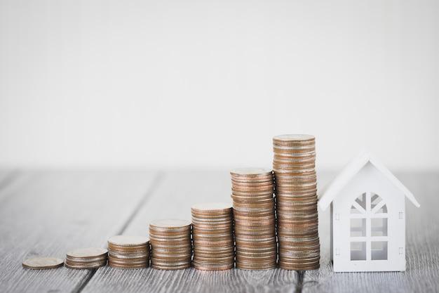 Pile d'argent de pièce intensifier la maison blanche, investissement immobilier et hypothèque de maison financière