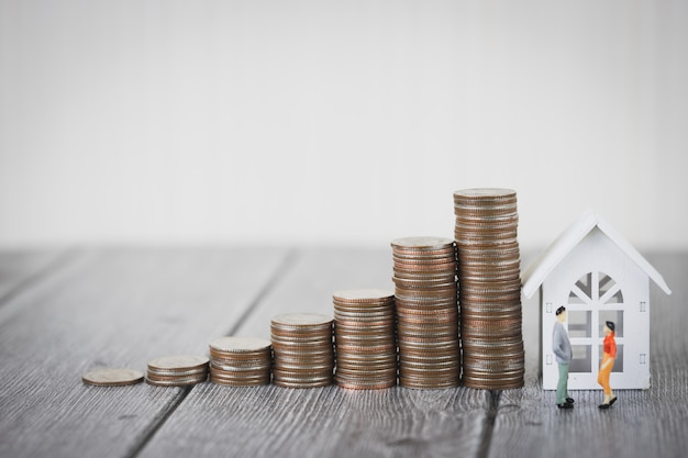 Pile d'argent de pièce intensifier avec la maison blanche, investissement de propriété et financier d'hypothèque de maison