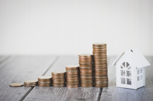 Pile d'argent de pièce de monnaie intensifier la maison blanche, investissement de propriété et hypothèque de maison financière