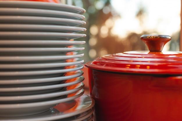Une pile d'assiettes blanches et une casserole rouge