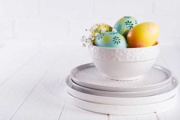Pile d'assiettes et bol avec des oeufs de pâques colorés, décoration de pâques au printemps sur une table en bois blanc