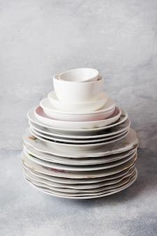 Pile d'assiettes propres vides sur une table grise avec espace de copie.