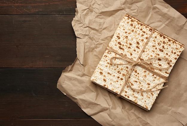 Pile bandée de matzoh carré cuit sur papier brun, vue du dessus
