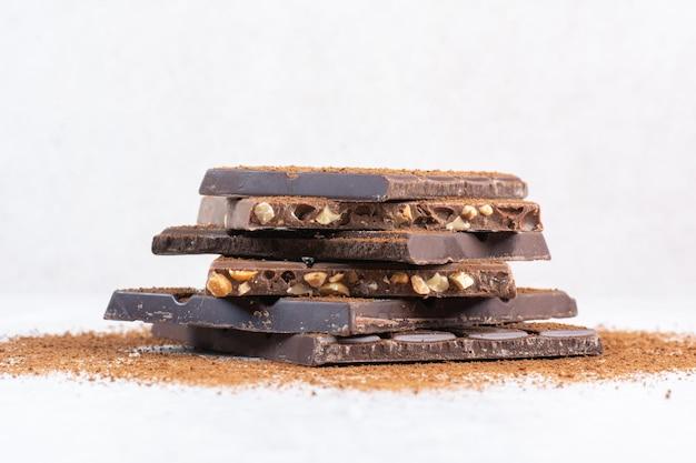 Pile de barres de chocolat décorées de poudre de cacao. photo de haute qualité