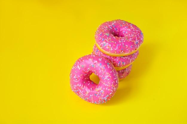 Une pile de beignets avec du glaçage rose sur une vue latérale du mur jaune. mal bouffe. bonbons, pâtisseries. calories, matières grasses.