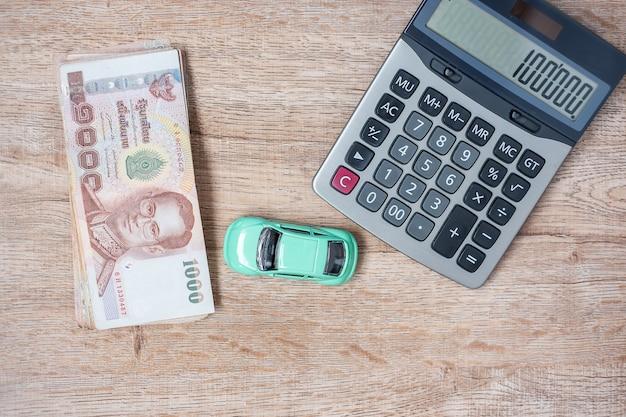 Pile de billets de baht thaïlandais avec voiture et calculatrice.