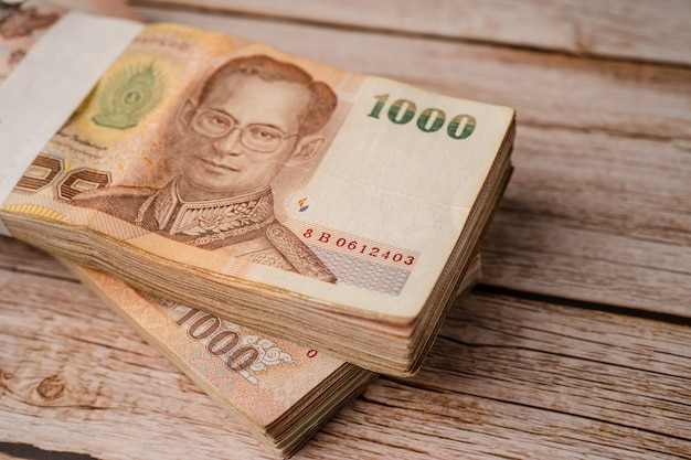 Pile de billets de banque en baht thaïlandais sur fond de bois, concept d'investissement financier d'économie d'entreprise.