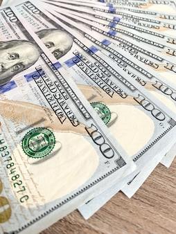 Pile de billets de cent dollars sur le bureau en bois