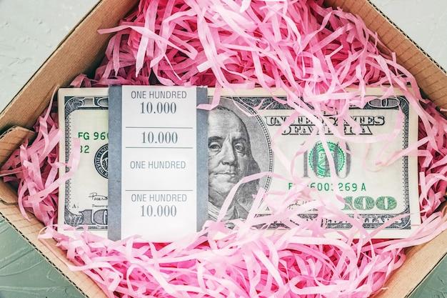 Pile de billets de cent dollars dans une boîte cadeau vue de dessus gros plan