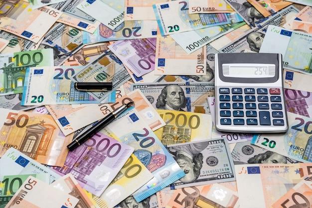 Pile de billets en dollars et en euros avec calculatrice