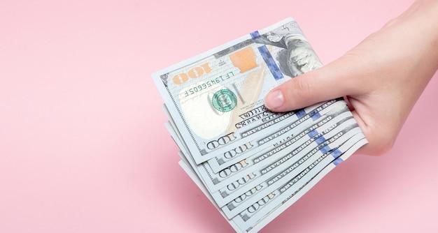 Pile de billets en dollars en main féminine sur rose