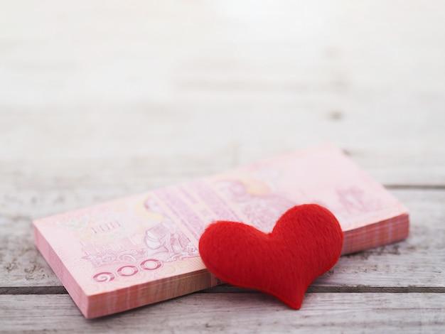 Pile de billets thaïlandais et coeur sur table en bois