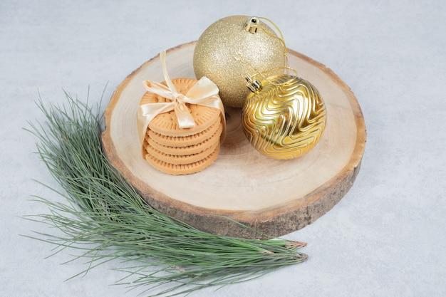 Pile de biscuits attachés avec ruban et boules de noël sur planche de bois. photo de haute qualité
