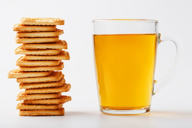 Une pile de biscuits au blé doré et une tasse de thé vert parfumé sur fond gris