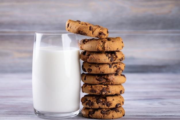 Une pile de biscuits aux pépites de chocolat se trouve près d'un verre de lait. lait riche en calcium.