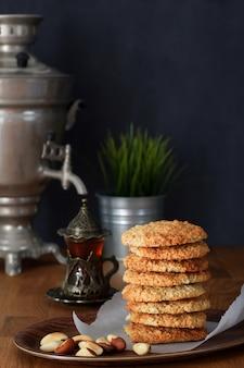 Pile biscuits à l'avoine avec des noix et du thé noir au samovar sur une table en bois