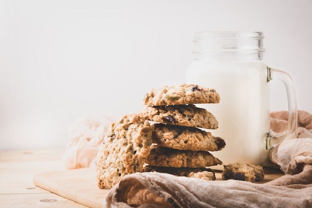 Une pile de biscuits à l'avoine et une tasse de lait sur un mur clair. fermer.